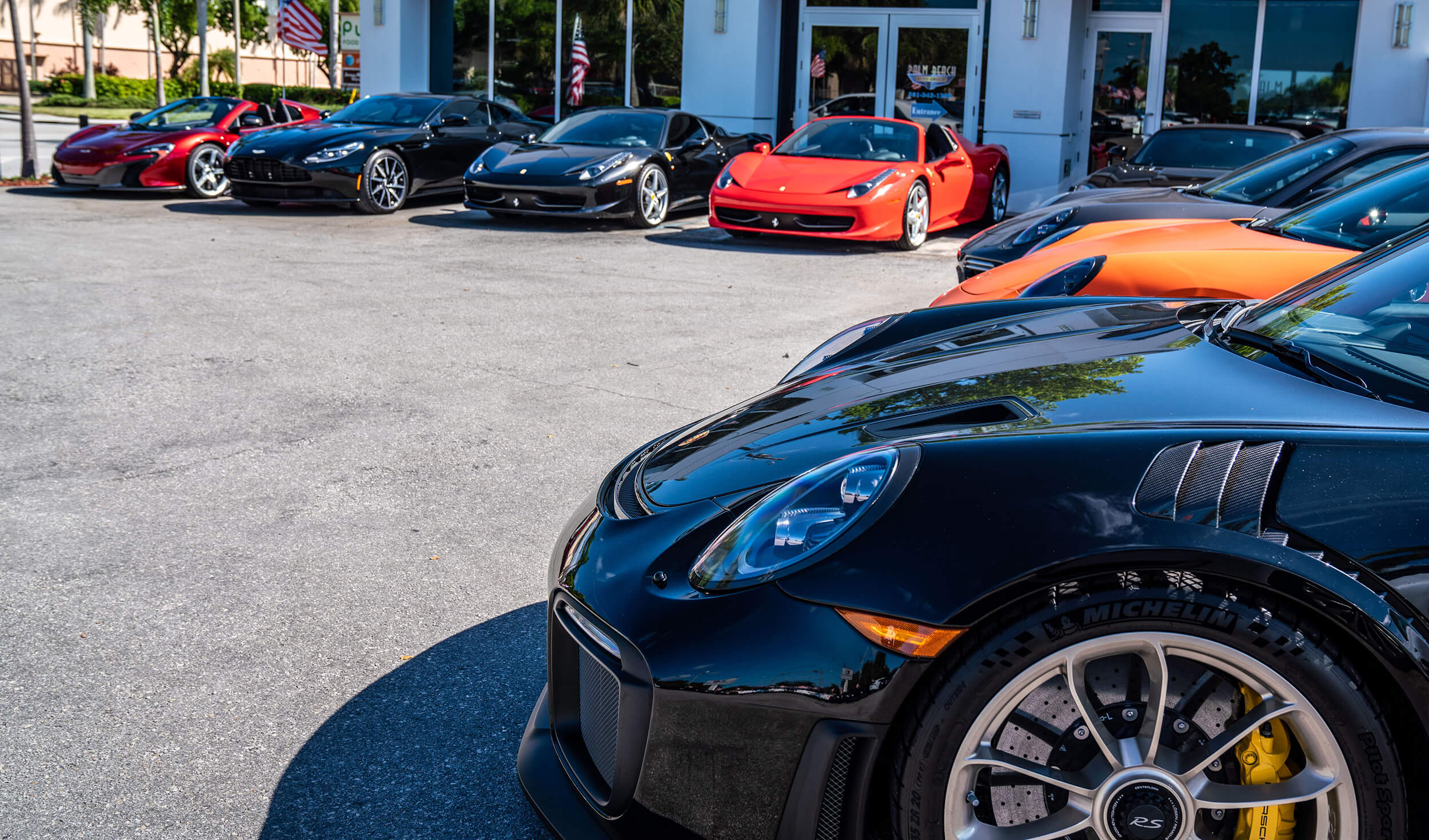 Exterior image of Palm Beach Auto Group dealership: front of store with exotic cars.